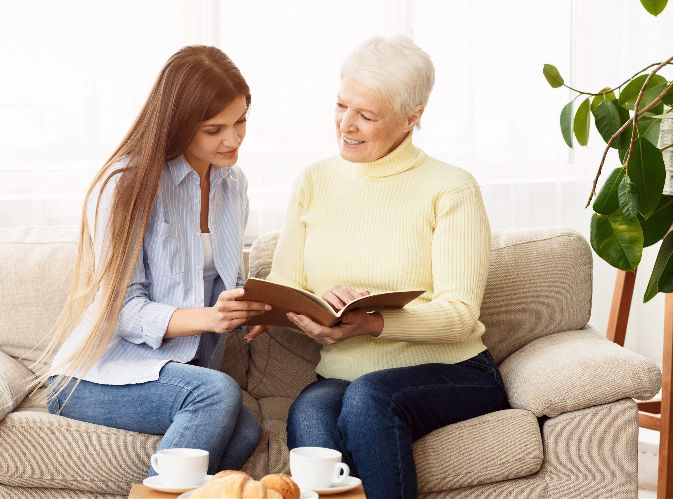 elderly-woman-looking-family-album-with-her-daught-TF6LBGQ-min
